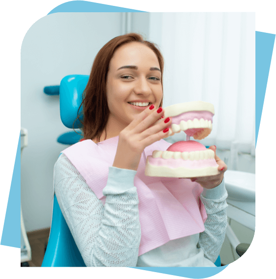 Woman sitting in a dental chair holding a mouth model.