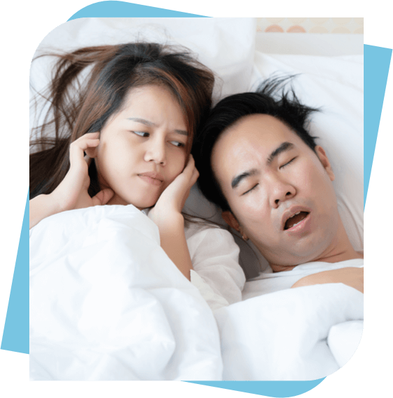 Asian woman plugging her ears with her fingers while her partner snores.
